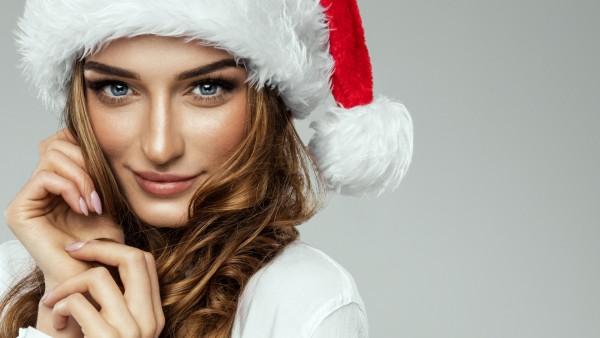 Новогодние обои девушка в шапке Санта-Клауса