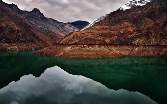 Зеркальное зеленое озеро и высокие горы