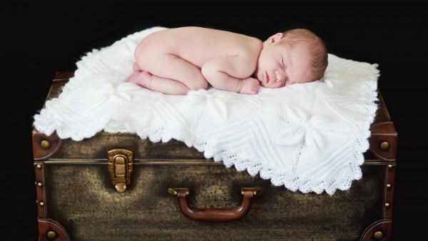 Валпиксинка маленького ребенка спящего на сундуке