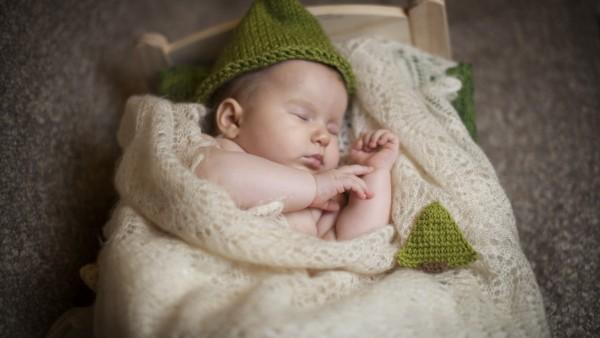 Обои спящего малыша в зеленой шапочке