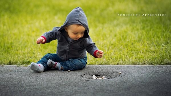 Прикольный малыш в балахоне на асфальте