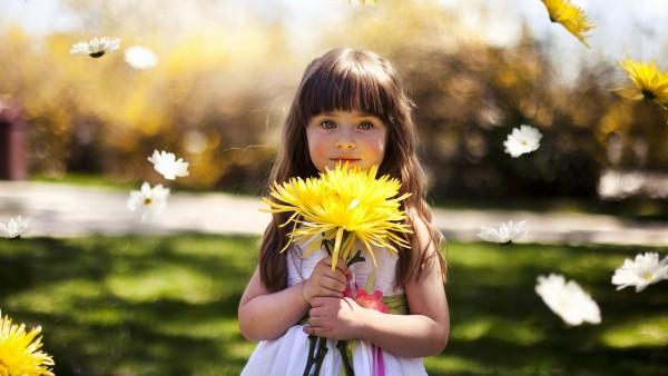 Маленькая девочка с желтым цветком обои
