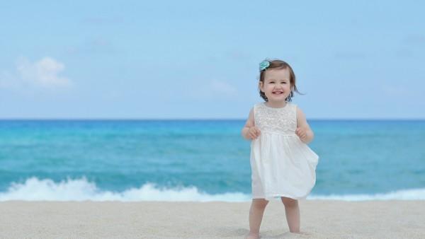 Обои малышки в платичке у моря
