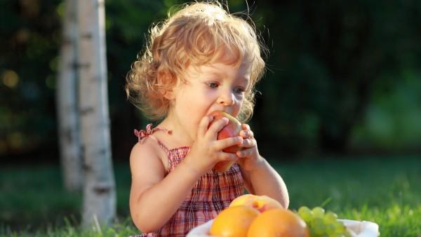 Кучерявая девочка кушает фрукты бесплатно картинки