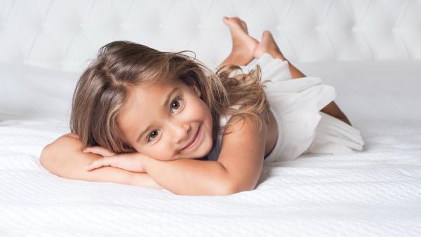Улыбающаяся девочка лежит на кровати картинки