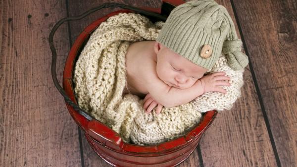 Ребенок спит в кравсном ведре надувши щеки
