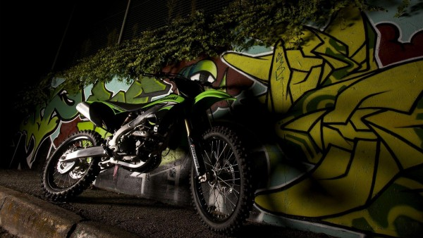 Зеленый мотоцикл Kawasaki KX250F на улице