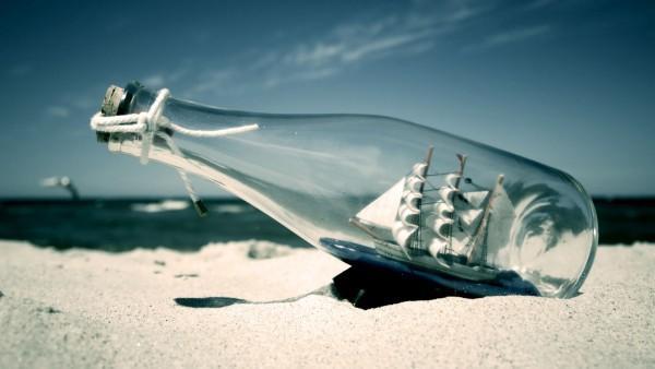 Корабль в бутылке на фоне моря фоновые обои на комп