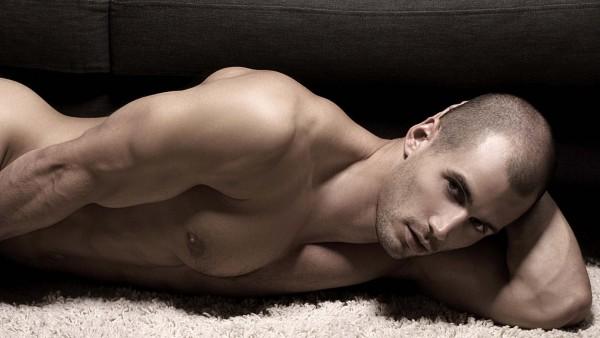 Обнаженный красавчик лежит на диване