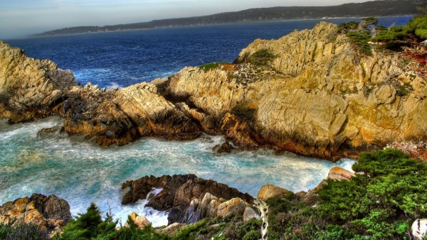 Широкоформатная заставка моря которое расположилось у высоких скал