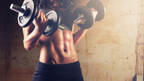 Девушка в спортзале с гантелями