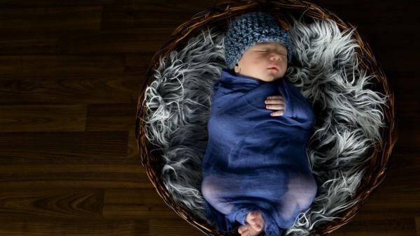 Маленький младенец в шапке спит в корзине