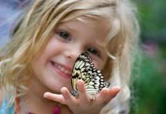 Маленькая улыбающаяся девочка держит в руках бабочку