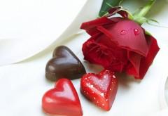 Конфеты в виде сердечек и красная роза на день Святого …
