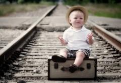 Ребенок на чемоданах на железнодорожных рельсах