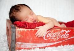 Маленький ребенок спит на бренде Кока-Кола