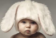 Ребенок в шапке кролика надул щеки скачать обои