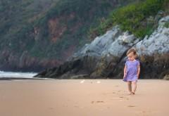 Маленькая девочка гуляет босиком по песчаной набережной