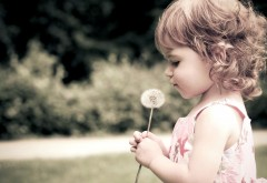 Маленькая девочка с одуванчиком в руках