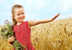 Милая маленькая девочка в пшеничном поле с букетом цве…