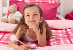 Мечтательная девочка на кровати пишет в блокноте