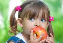 Девочка с голубыми глазами кушает красное яблоко