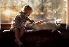 Маленький ребенок играется с белым кроликом