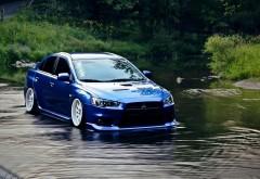 Фото синего автомобиля марки мицубиси лансер едущий п�…