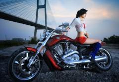 Фото девушки азиатки сидящей на красно-черном мотоцикле марки харлей