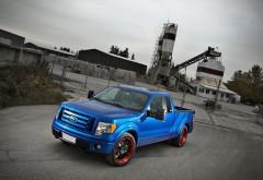 Фото синего автомобиля марки Ford стоящего около какой-т…