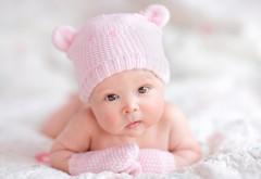 Маленький ребеночек в шапочке с ушками и перчаточках