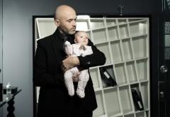Маленький ребенок на руках у мужчины в костюме
