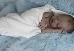 Новорожденный малыш спит укутавшись на пушистой крова…